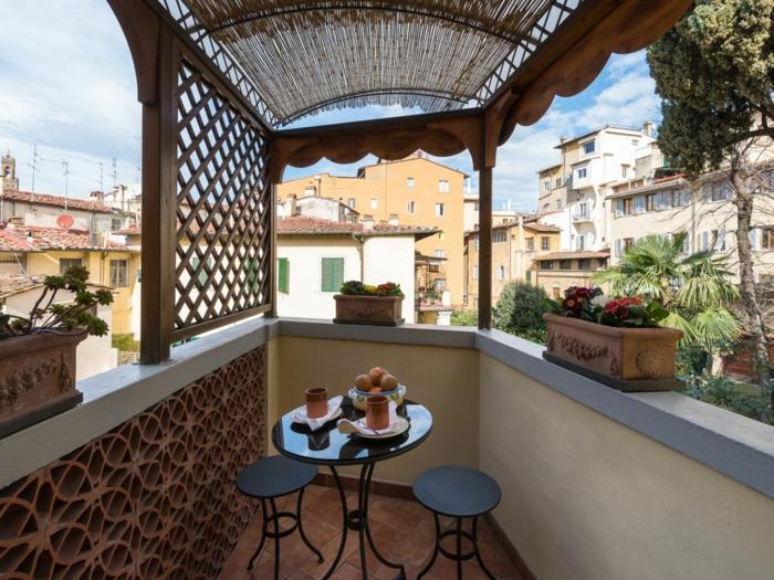 bonita terraza con poca decoración y macetas vintage de arcilla con flores, pequeños muebles en negro