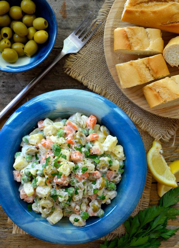 ensaladilla rusa adornada de aceitunas verdes y tostadas, ideas de recetas fáciles y ricas para picoteo