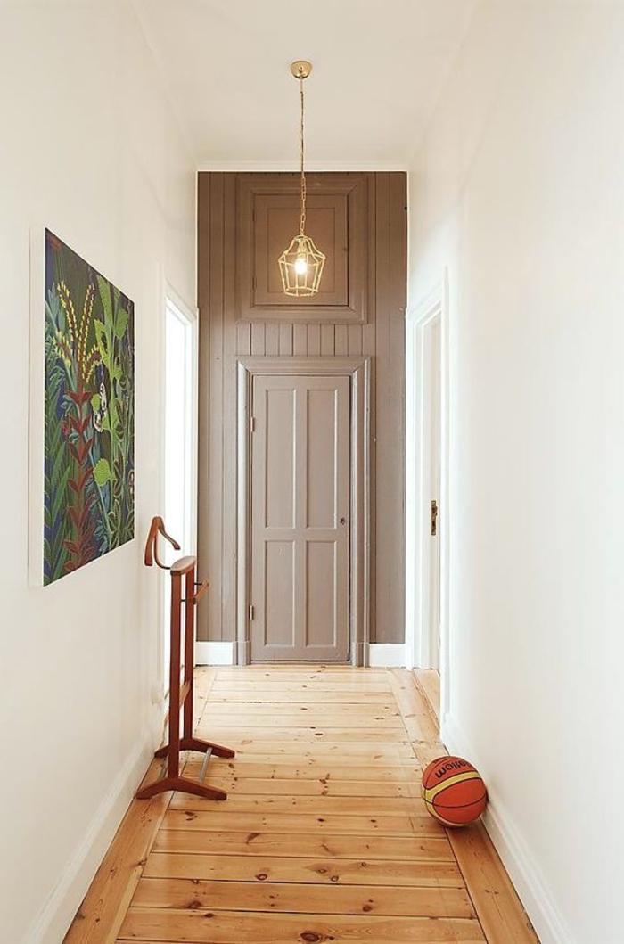 pasillo de encanto con suelo de parquet paredes en blanco y grande puntura, lámpara en estilo vintage