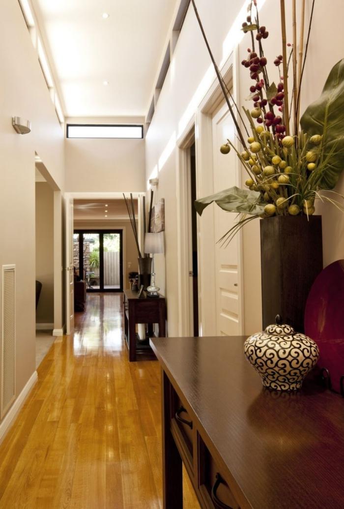 largo y estrecho pasillo decorado en beige claro con suelo de parquet y flores artificiales, pintar pasillo moderno