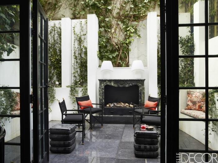 decoracion terrazas, porches y patios, precioso espacio decorado en negro y gris con chimenea de leña y cojines decorativos en rojo