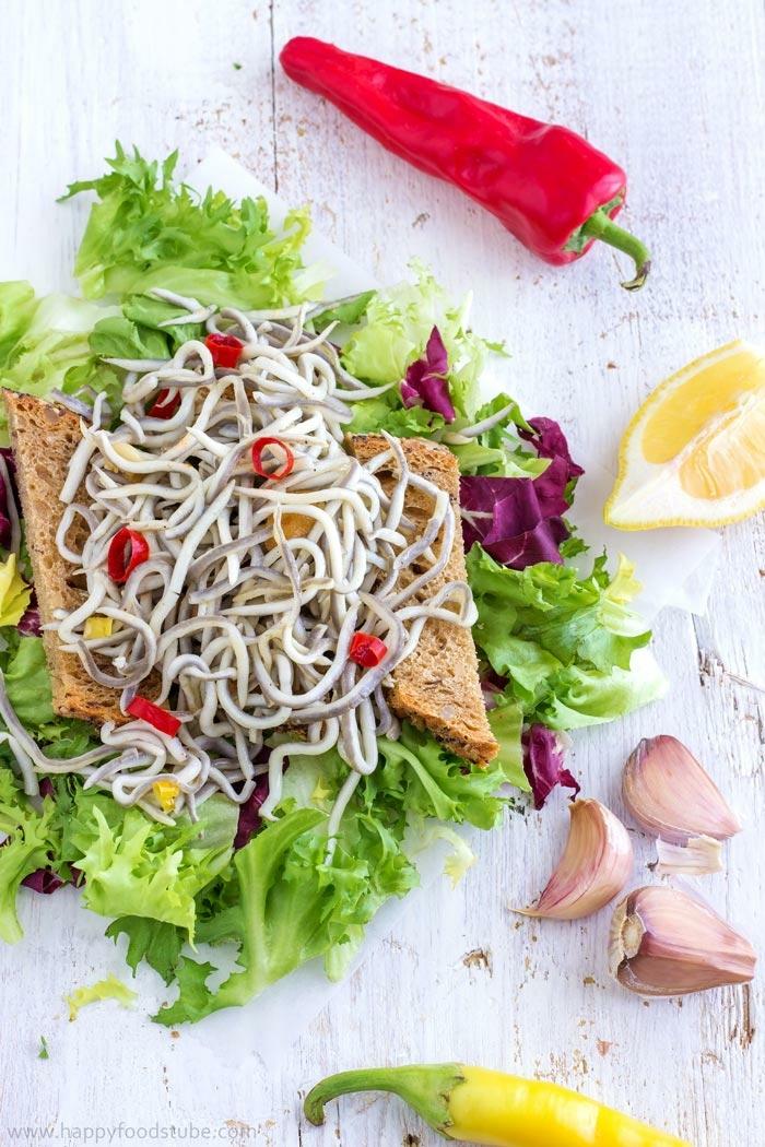 ricas ideas de entrantes faciles para sorprender, tostadas con anguilas, ajo, pimientos rojo y amarillo y lechuga