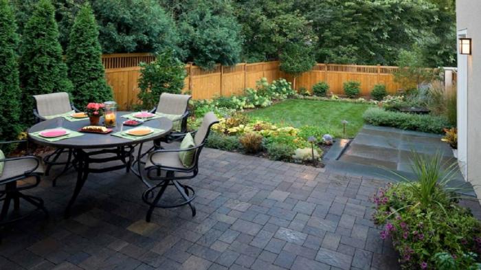 ideas de decoracion exteriores de diseño, grande mesa oval con sillas modernas, suelo con pavimento y pequeño jardín
