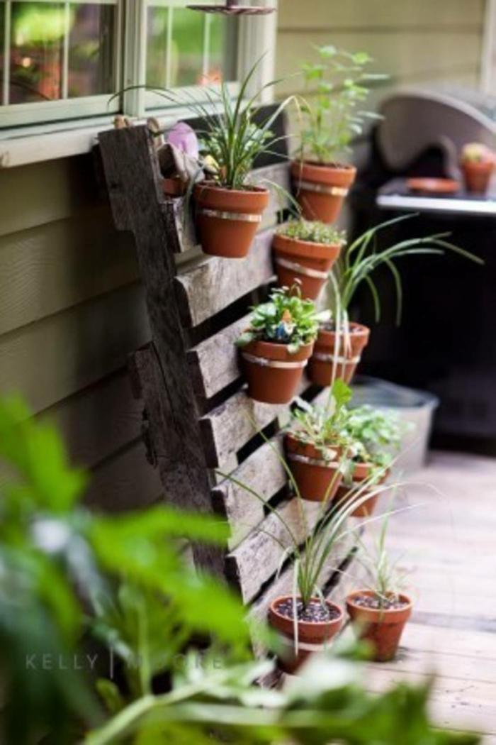 bonitas ideas con palets, macetas pequeñas colgadas al palet, decoración con plantas verdes