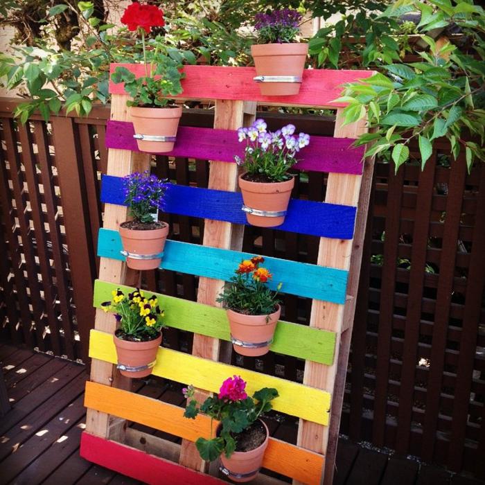 preciosa decoración para tu jardín con palet pintado en diferents colores y pequeñas macetas con flores