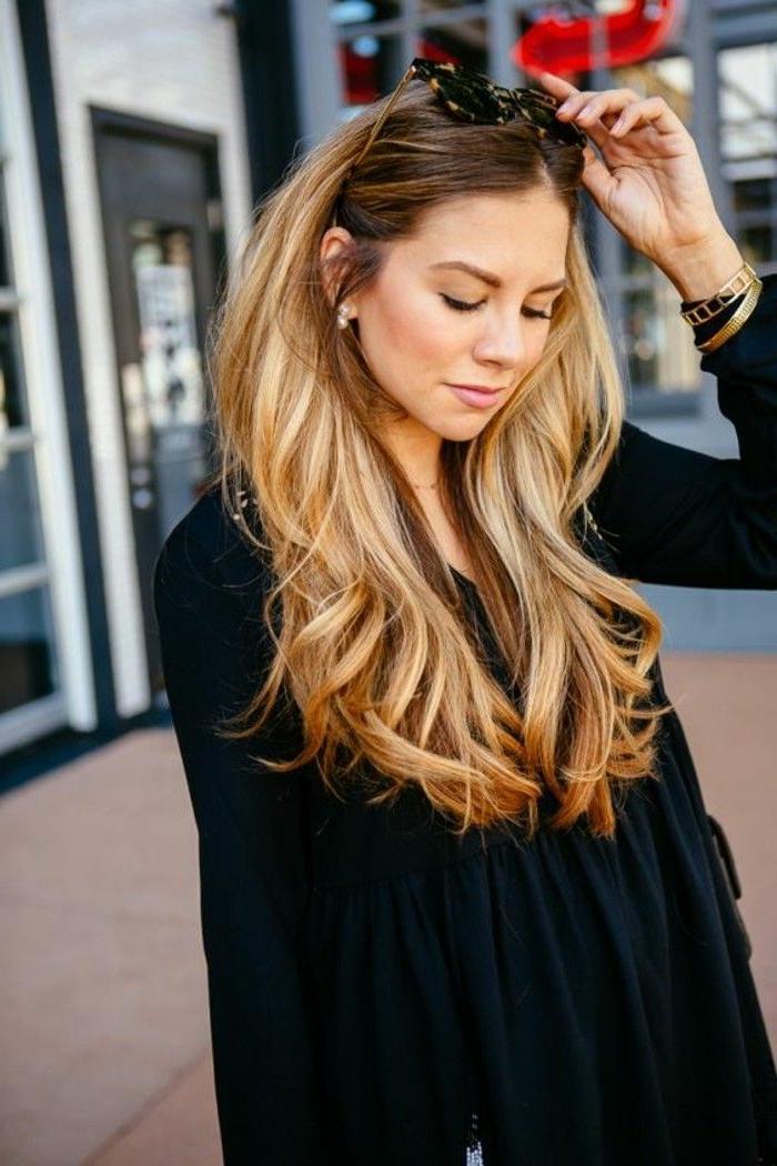 corte de pelo en capas, cabello rubio oscuro con mechas más claras y puntas onduladas, pelo peinado hacia atrás
