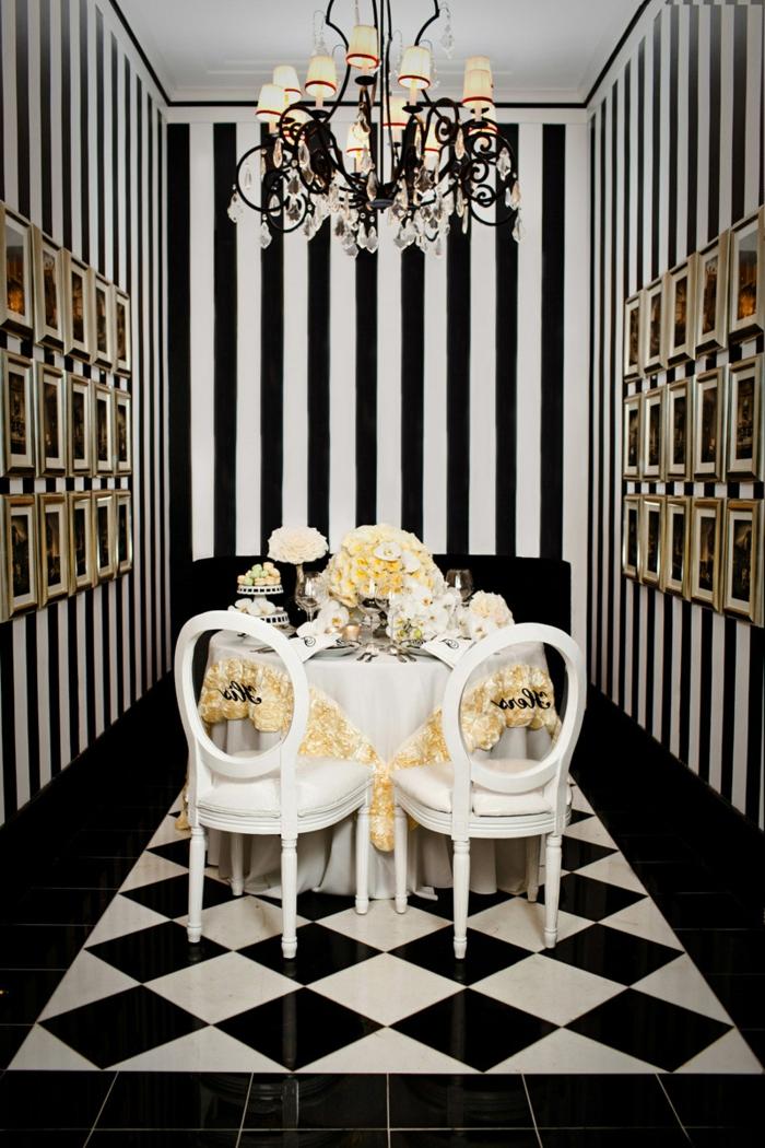 comedor elegante, paredes decoradas con papel pintado rayas en blanco y negro, candelabro vintage y suelo con azulejos