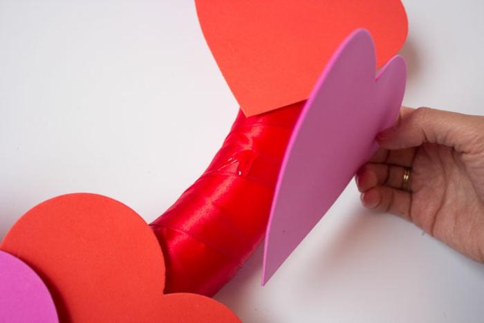 como hacer una corona goma eva decorativa con corazones de goma eva, pegar los corazones al aro de plástico