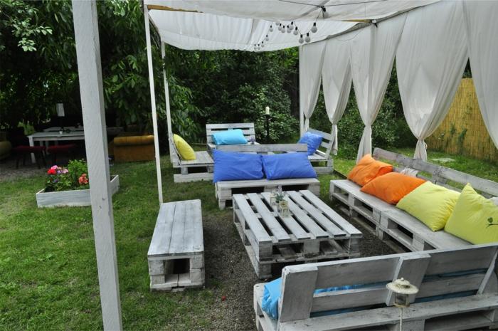 ideas para decorar jardines grandes y a patios, pergola de madera con muebles DIY hechos con palets y cojines decorativos