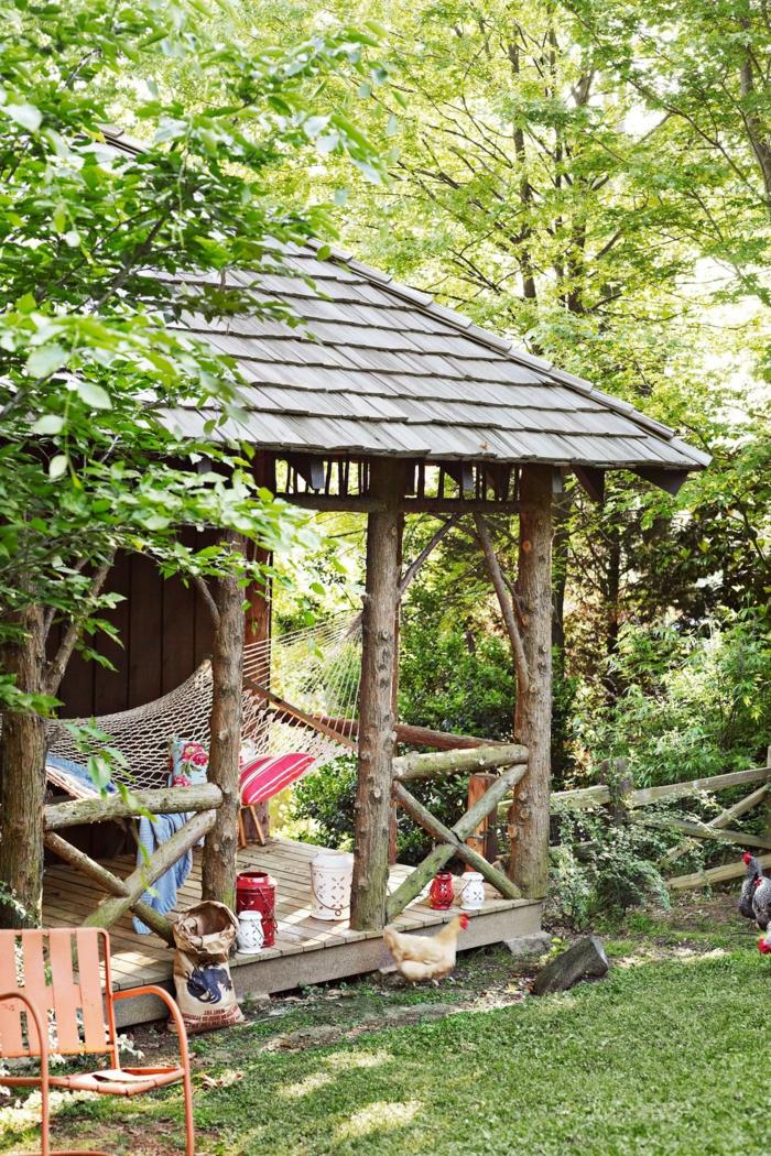ideas para decorar terrazas en estilo rústico, pequeña casa en el bosque de madera con hamaca en el porche
