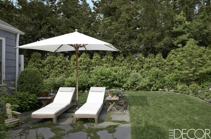 ideas de decoración de patios con encanto, grande jardín con césped y sillones modernos en blanco