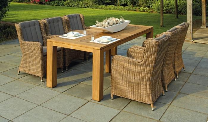 decoracion porches y patios, muebles modernos, mesa de madera y sillas de mimbre y suelo de baldosas