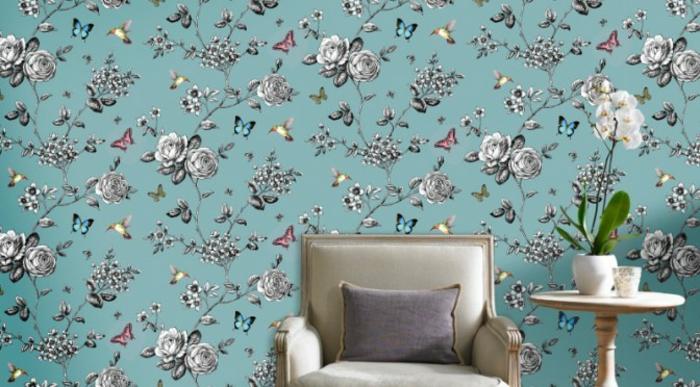 salón precioso decorado en tonos claros, pared con papel pintado motivos florales, sillon en beige y pequeña mesa de madera