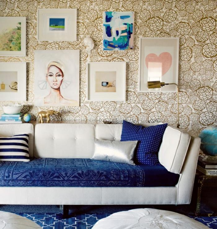 salón de encanto decorado en estilo vintage con muchos cuadros decorativos, sofá en beige con cojines decorativos en azul
