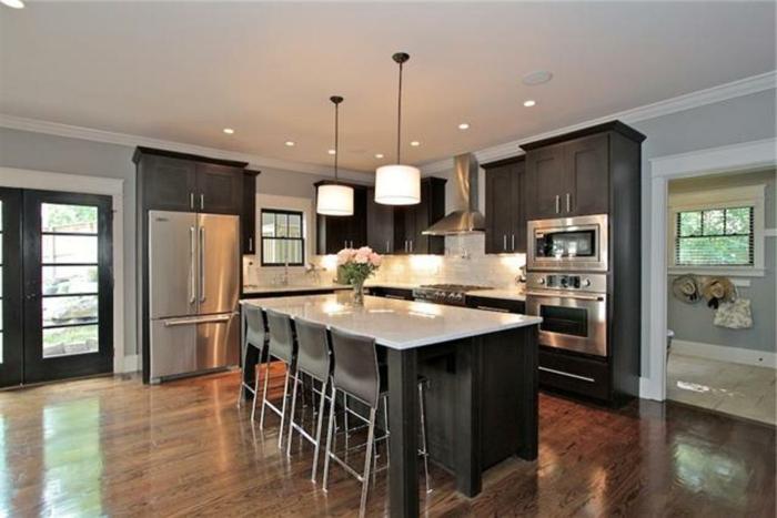 decoracion cocinas grandes abiertas al salón con isla, iluminación discreta y armarios en color oscuro