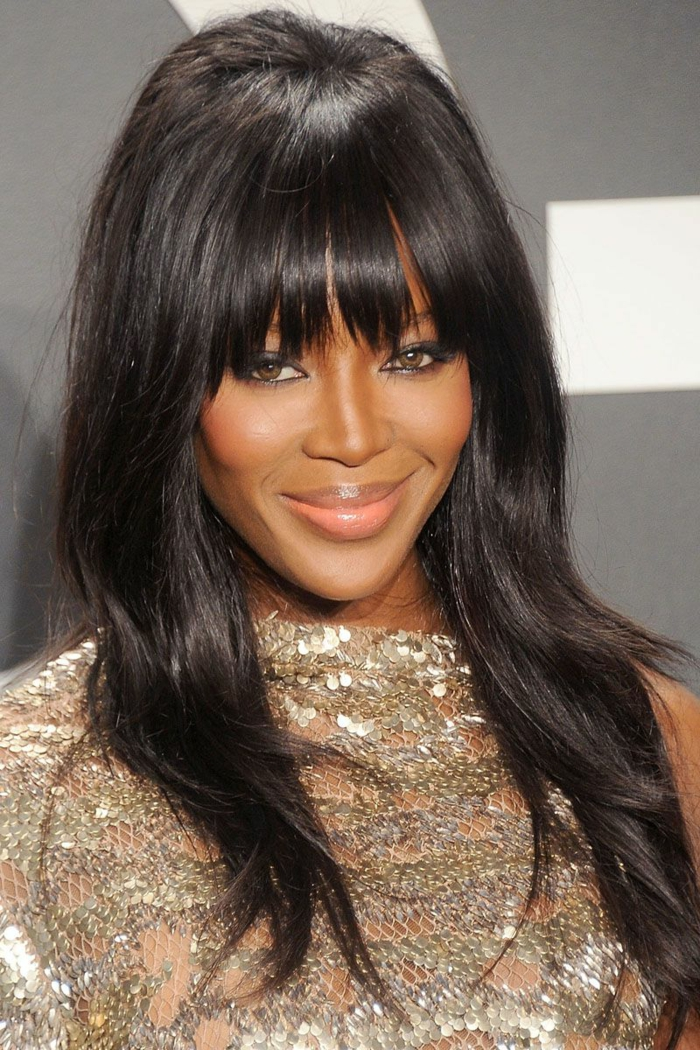 Naomi Campbell tendencias cortes de pelo para cara alargada, pelo largo castaño oscuro con flequillo moderno