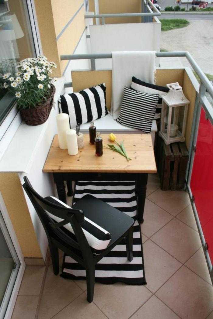 pequeña terraza con comedor externo, muebles de madera y detalles decorativos en rayas, ideas para decorar terrazas