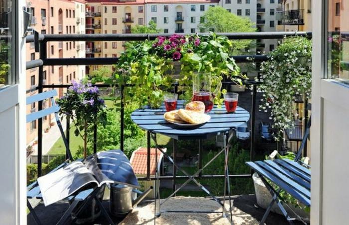 preciosa terraza con plantas verdes, flores y pequeño comedor exterior con muebles de madera, ideas para decorar terrazas