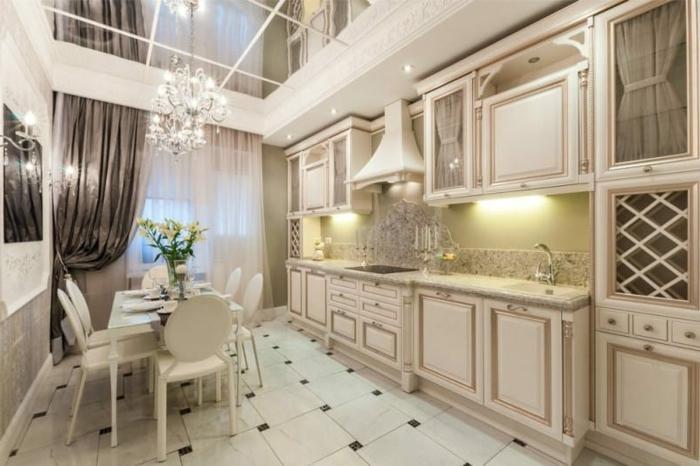 cocina de alto coste en estilo barroco con mesa blanca con sillas y techo con espejos, barra americana