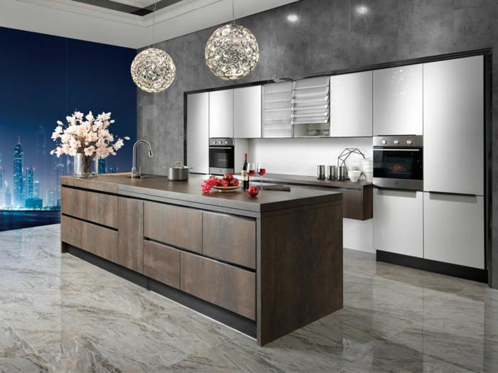 cocina moderna con isla de madera en marrón oscuro, con jarrón de flores rosas encima y lámparas redondas