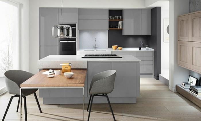 cocina en gris con suelo de parquet marrón claro, mesa de madera y una ventana grande