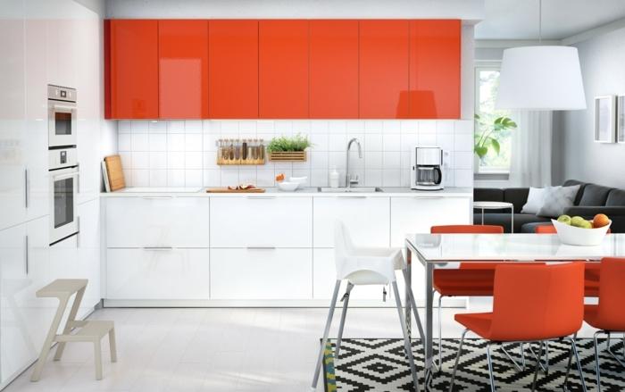 cocina americana en colores blanco y naranja, con alfombra con figuras geométricas y lámpara blanca colgante