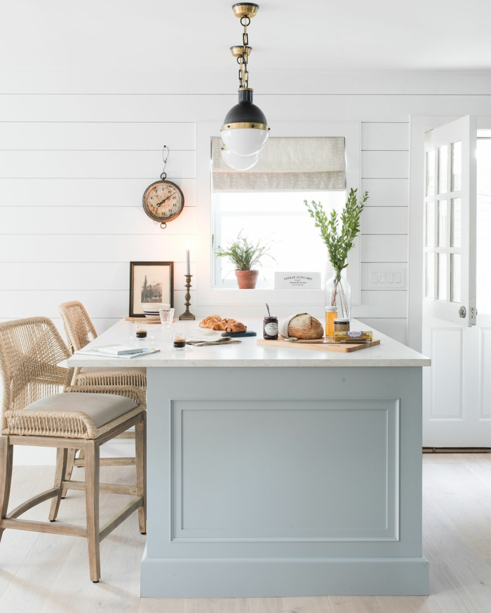 cocinas americanas con isla con encimera blanca y cajones de azul claro, sillas de ratán y madera altas