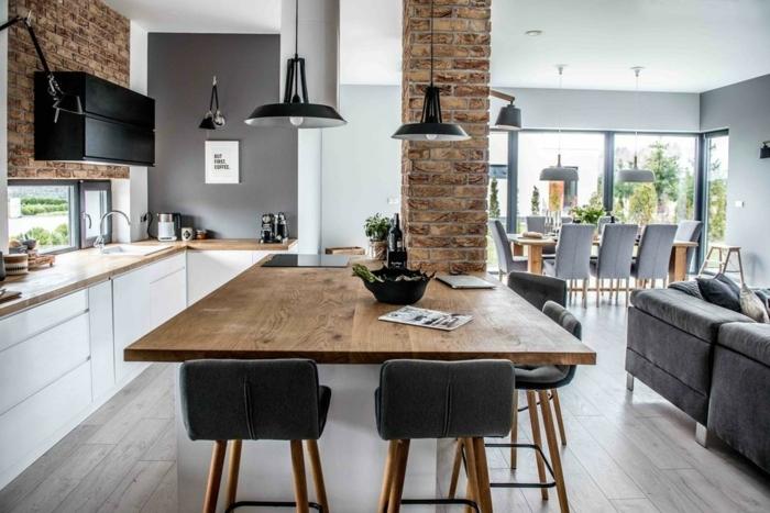 combinación de colores marrones con el gris y el negro, suelo de parquet, sofa gris con cojínes y ventanas grandes