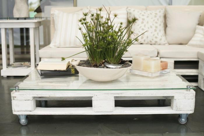 mesa con palets pintada con pintura blancay con vidrio sobre ella sujeto con elementos metálicos