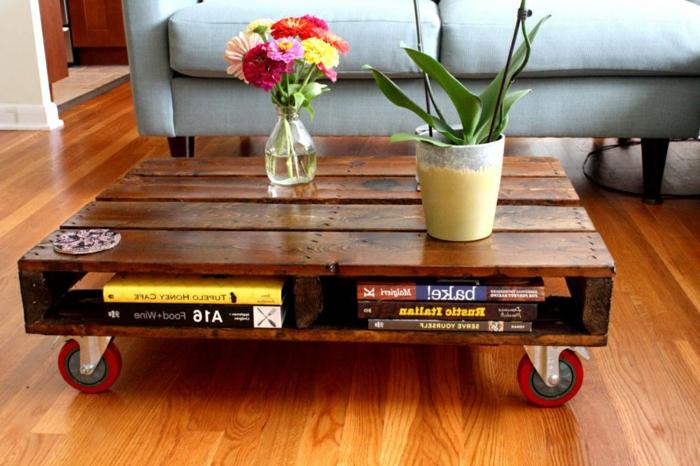 mesa bajita de salón en marrón oscuro con ruedas rojas y con jarrón con flores encima, mesa de palets