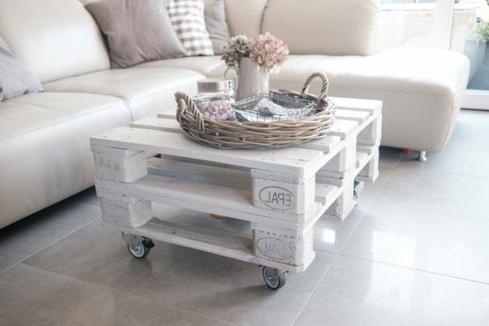 mesa pequeña de salón en color blanco pintada, hechas de dos palets con ruedas y con flores encima