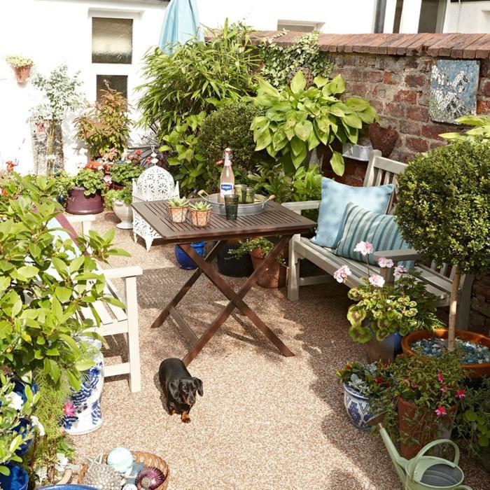 precioso patio con mucha vegetación y muebles de madera, como decorar un jardin pequeño paso a paso