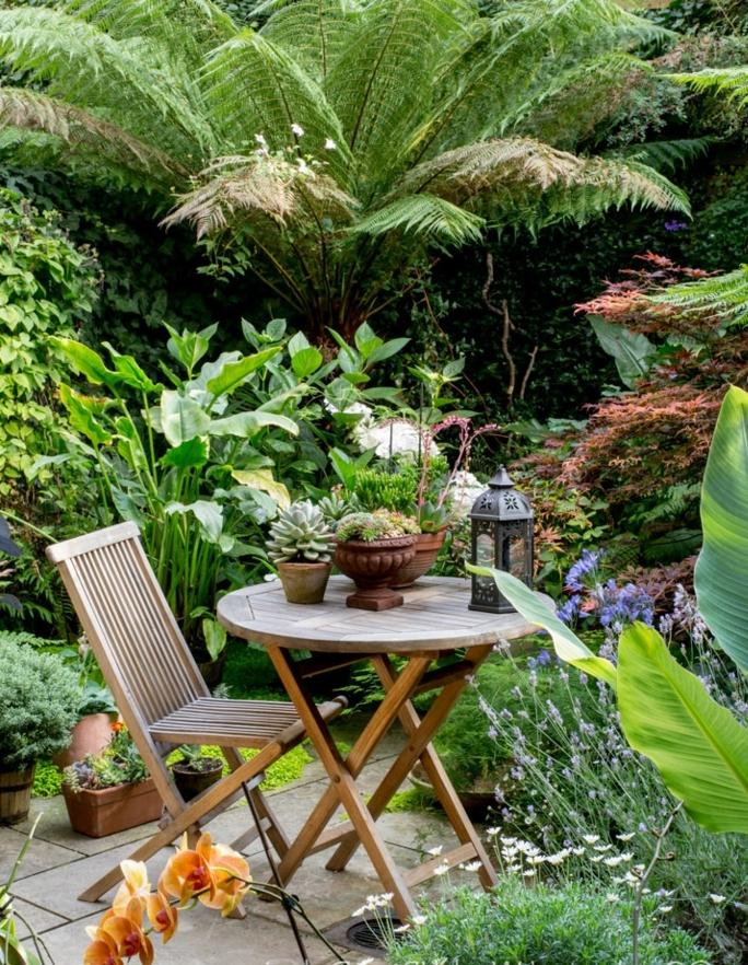 precioso rincón de relax decorado con muebles de madera, suelo de baldosas y mucha vegetación