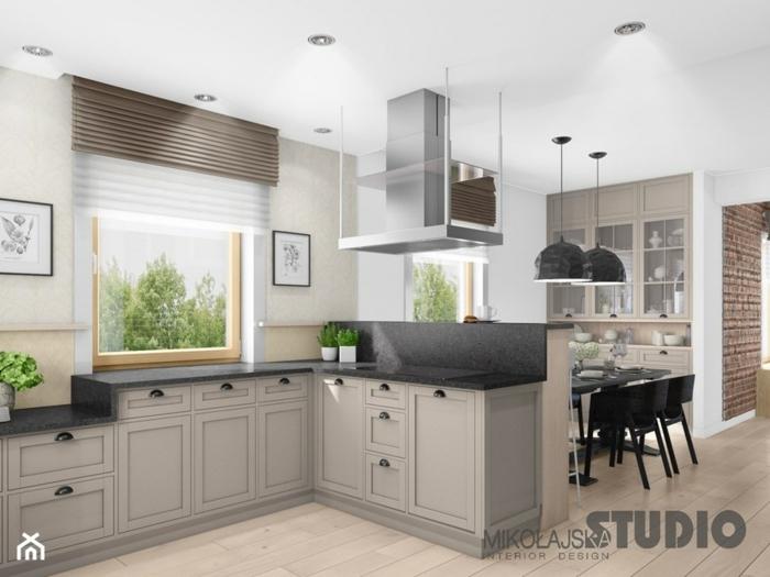 cocina con armarios en beige y encimera en negro con ventana grande al lado , barra americana