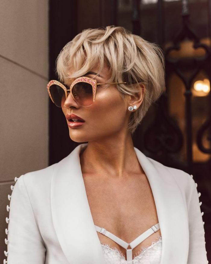 cortes de pelo mujer, con gafas de ultima moda con puedras swarovski por los bordes en color salmon y con blazzer blanco con botones en la mangas