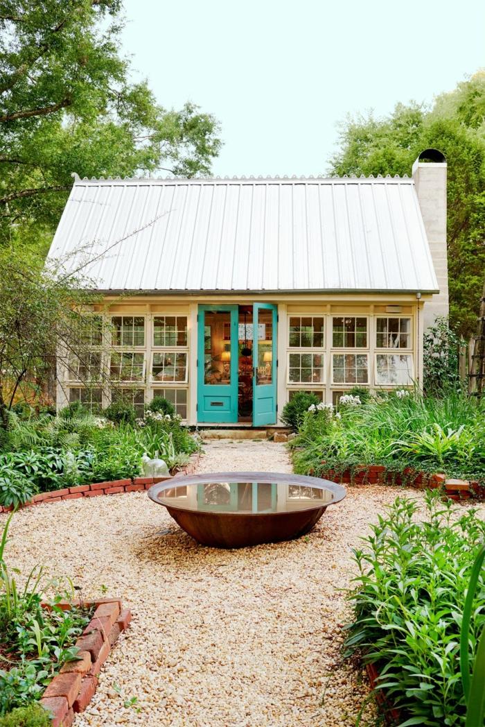 pequeño jardín con fuente, suelo con gravilla en color beige, ideas sobre como decorar un jardin pequeño
