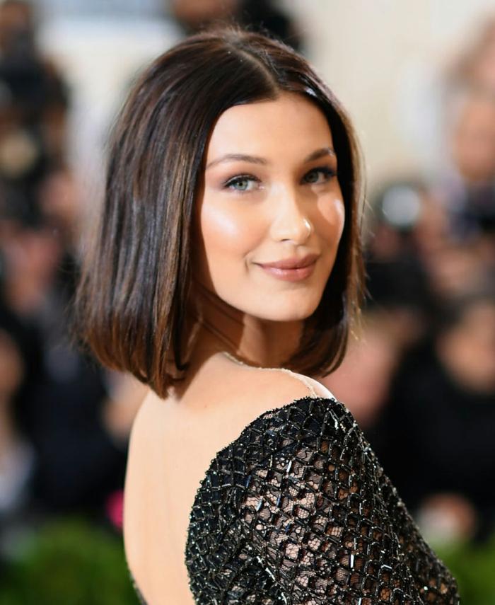 cortes de pelo corto mujer, Bella Hadid con vestido negro con la espalda al descubierto y melena cortita castaña