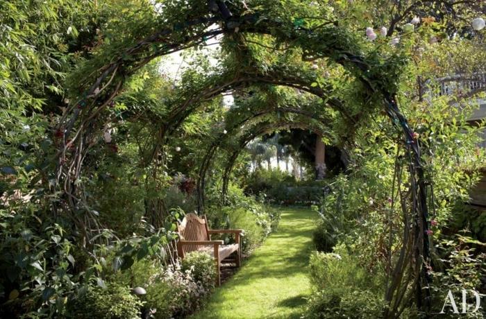 como decorar un jardin pequeño de maravilla, arcos de árboles, sendero con césped y banco de madera