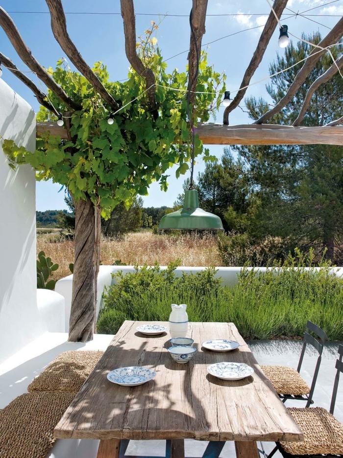 cómo decorar un jardín pequeño en estilo mediterráneo, muebles de madera y decoración en blanco