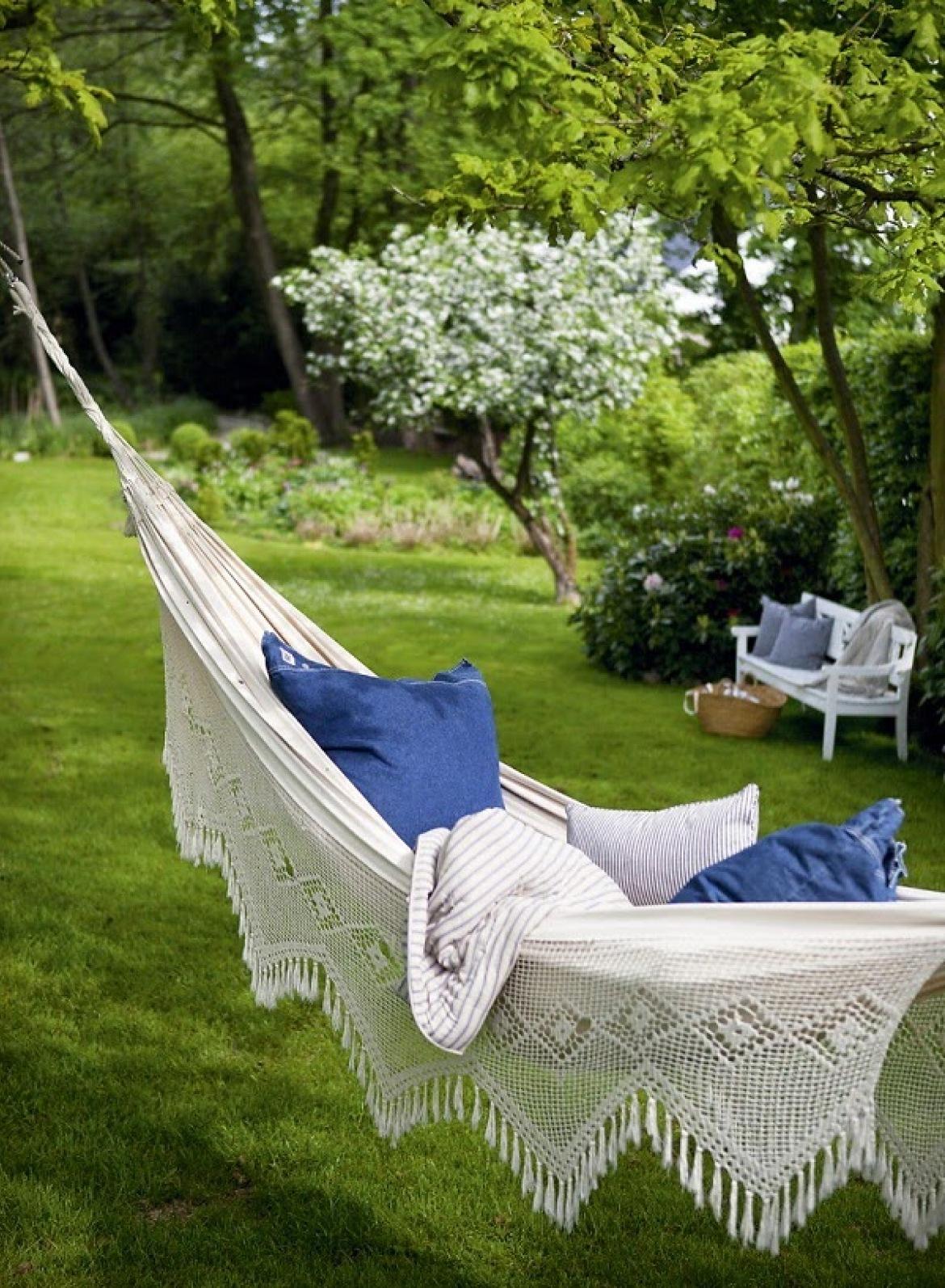 cómo decorar un jardín pequeño y cómodo, preciosa jamaca colgada en el jardín, suelo con césped y banco de madera