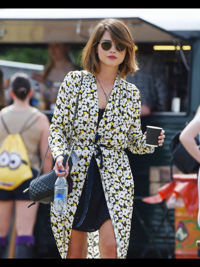 cortes de pelo corto mujer, chica con gafas de sol negras, redondas y capa con cinturon de flores en blanco,negro y amarillo combinada con vestido corto negro y bolso pequeño con cadena