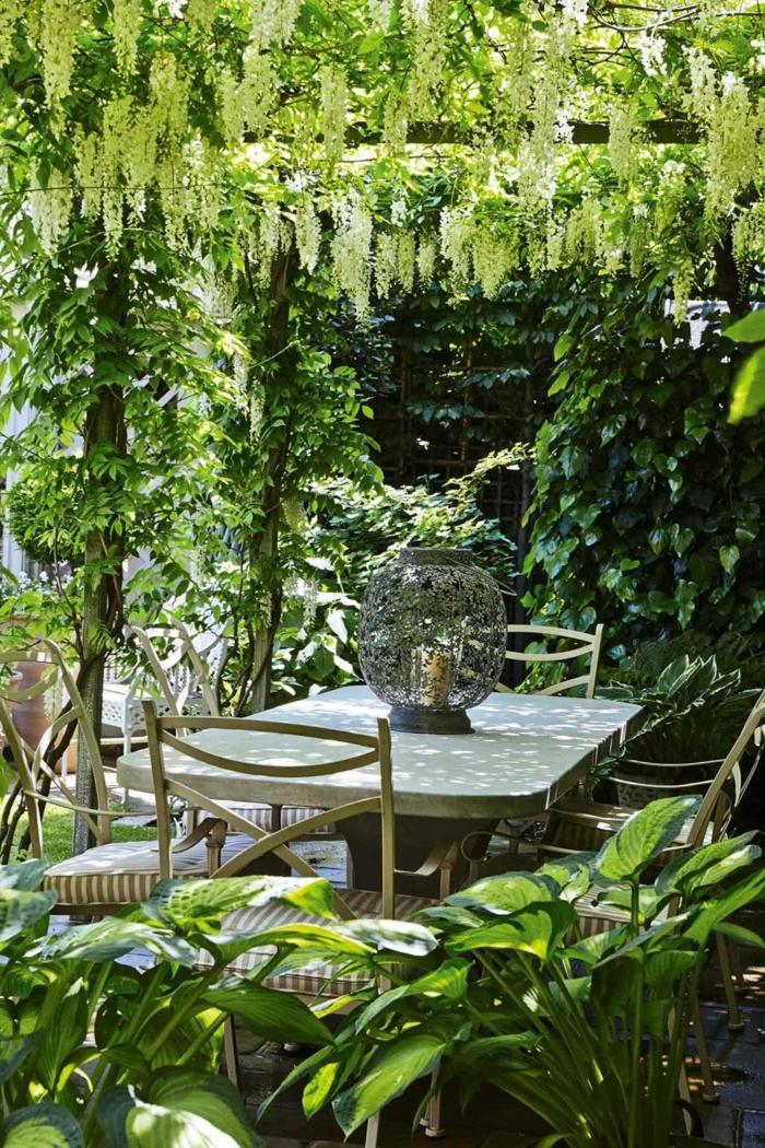 patio de encanto con mucha vegetación, cómo decorar un jardín pequeño, últimas tendencias en decoración de exteriores
