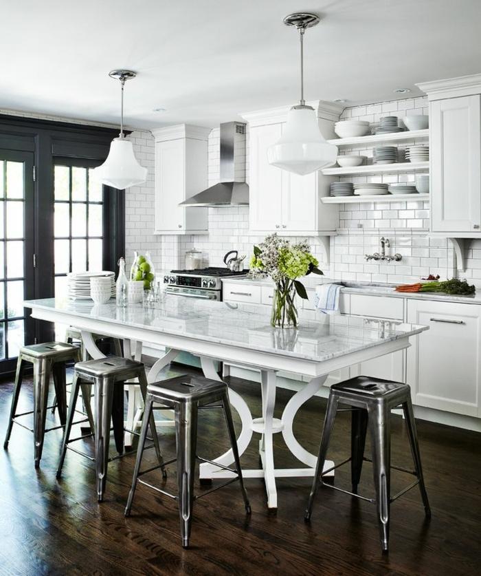 cocina moderna con mesa blanca con jarrones con flores encima y sillas de bar negras, salon cocina