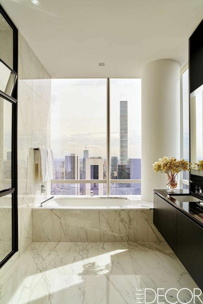 baño con vista decorado en blanco marmol, baños blancos modernos con azulejos de marmol y decoración de flores