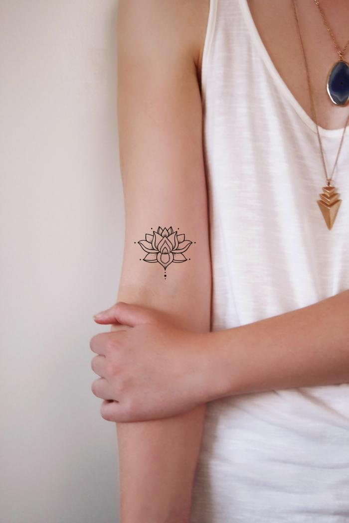 tatuajes simbolicos para mujeres, dibujo de loto en el brazo hecho con tinte negro, tatuajes con mensaje