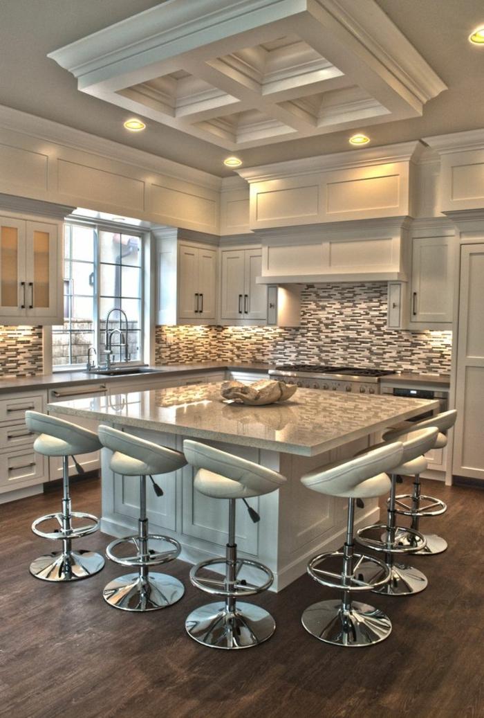 cocina con isla cuadrada en el medio con sillas de bar de cuero en color blanco y suelo de parquet marrón