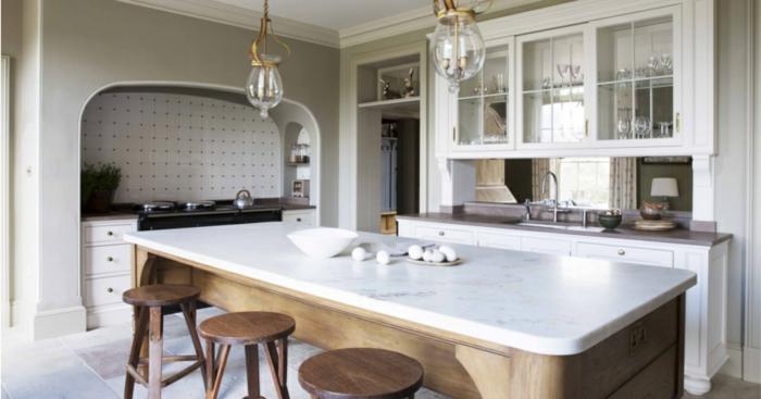 parte de la cocina donde se ve la mesa grande de mármol con las sillas de bar de madera