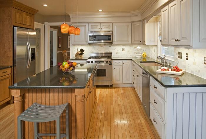 cocina en naranja, estilo americano de texas con armarios en blanco oscuro y lamapras naranjas, barra americana