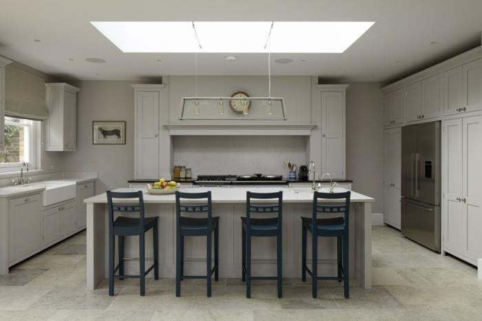 cocina de color blanco y beige con sillas azul oscuras y una lámpara rectangular grande en el techo