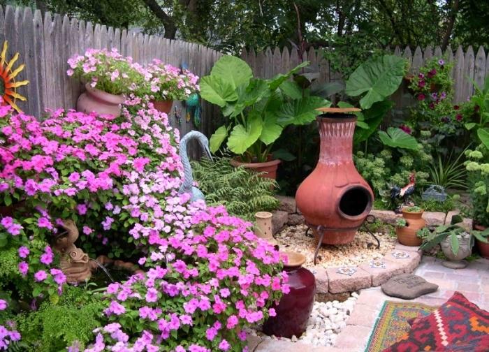 cómo decorar un jardín pequeño en estilo mediterráneo, muchas plantas con flores y decoración DIY